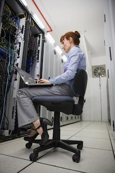 Техник, сидящий на поворотном стуле, используя ноутбук для диагностики серверов