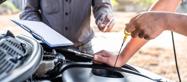 Команда техников, работающих автомехаником, занимается ремонтом автомобилей и ремонтным работником, ремонтирующим автомобиль с проверкой масла, обслуживанием и техническим обслуживанием автомобиля.