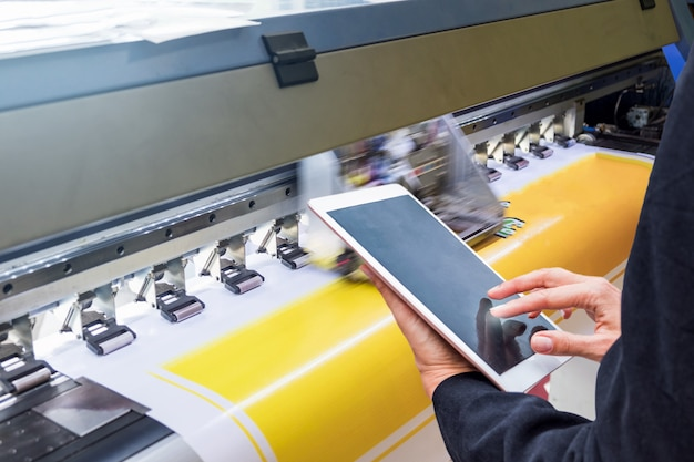 Technician touch control tablet on format inkjet printer during yellow vinyl