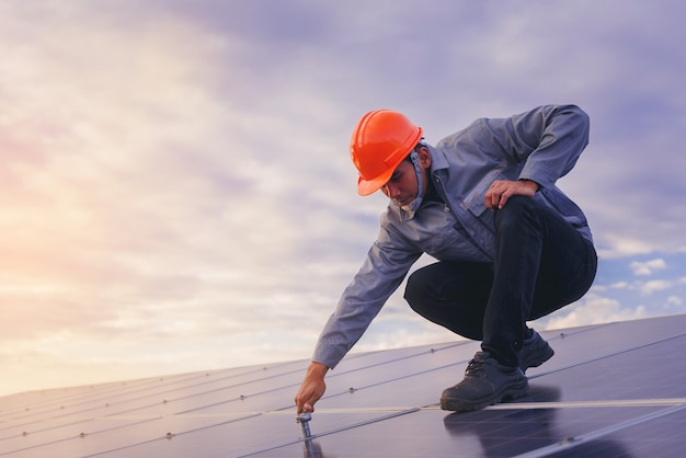 Technician use wrench to maintenance electric system at solar panel field with sunset sky