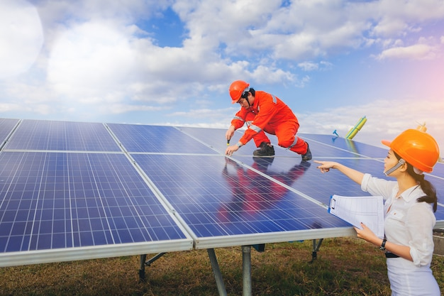 Technician use wrench to maintenance electric system at solar panel field.