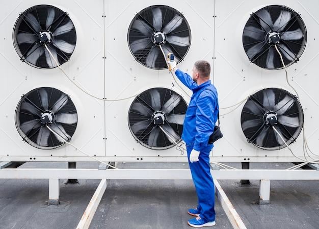 Техник использует тепловизионный инфракрасный термометр для проверки теплообменника конденсаторной установки.