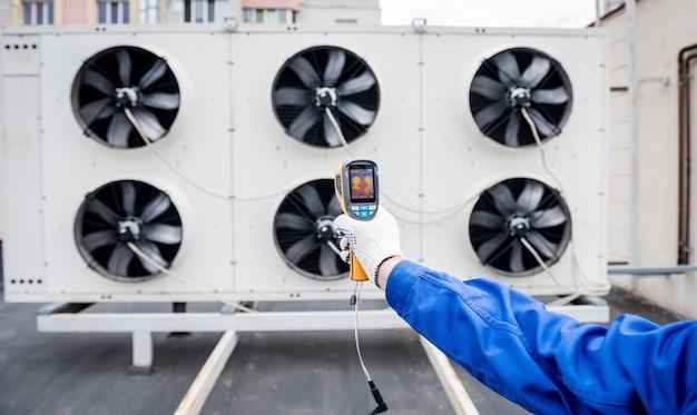 技術者は、熱画像赤外線温度計を使用して、凝縮ユニットの熱交換器をチェックします