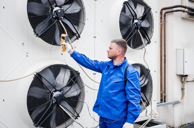 기술자는 열 화상 적외선 온도계를 사용하여 응축 장치 열교환기를 확인합니다.