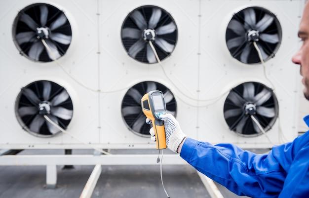 기술자는 열화상 적외선 온도계를 사용하여 응축 장치 열교환기를 확인합니다.