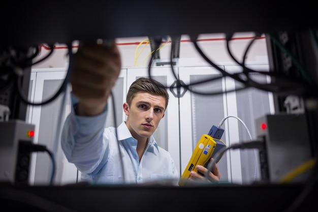 Technician using cable tester while fixing server