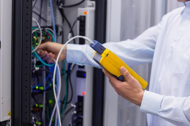 Техник, использующий цифровой анализатор кабелей на серверах