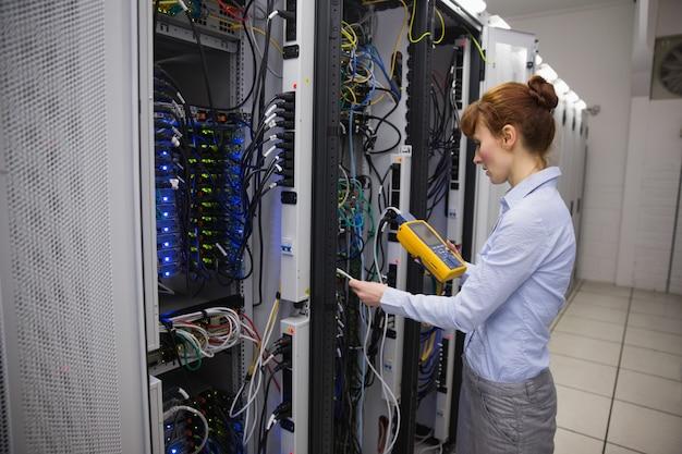 Техник, использующий цифровой анализатор кабеля на сервере