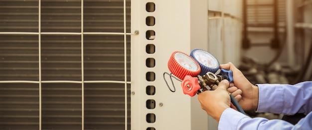 Техник, использующий коллектор для заполнения промышленных заводских кондиционеров.