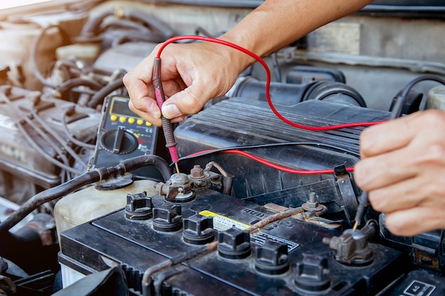 Technician using measuring equipment for checking car battery. concepts of car repair service and car insurance.