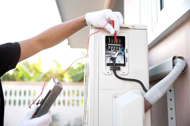 屋外空気圧縮機で電気をチェックする測定ツールを使用する技術者。
