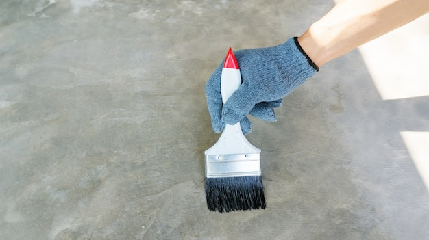 Technician using a varnish paint with a cement floor.