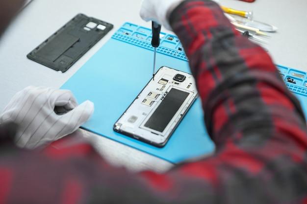 Техник в белых антистатических перчатках и клетчатой рубашке сидит за своим столом и с помощью точной отвертки откручивает винты на задней панели неисправного мобильного телефона