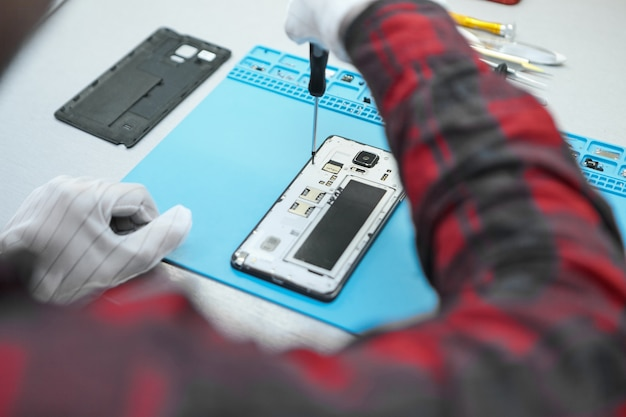 Technician wearing white antistatic gloves and plaid shirt sitting at his desk and using precision screwdriver to remove screws on back of faulty mobile phone