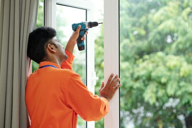 顧客の家に新しい大きな窓を設置するドリルを持った技術者