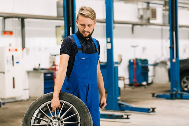 Technician with wheel in shop
