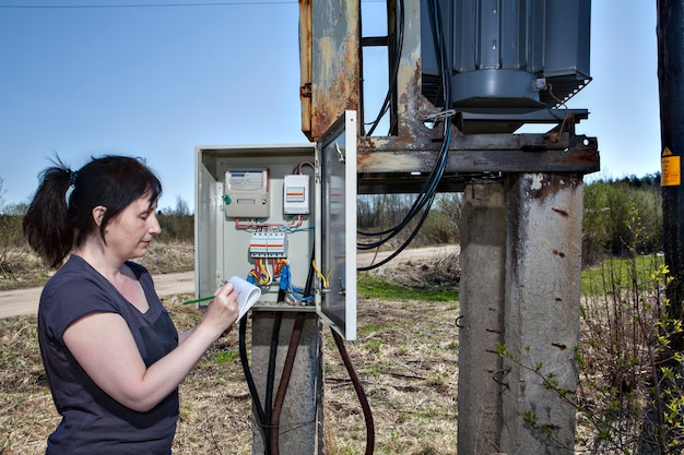 Technician woman checking electricity meter and invoice standing near electricity switchgear  power transformer substation outdoors.