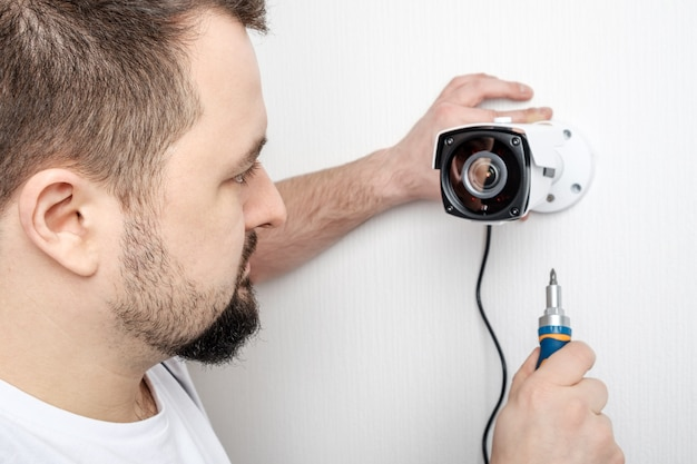 Technician worker installing video surveillance camera