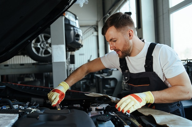 Technician working on checking and service car in  workshop garage
