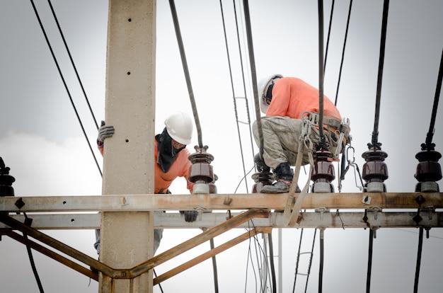 기술자들이 전주에 있는 고전압 전송 시스템을 수리하고 있습니다.