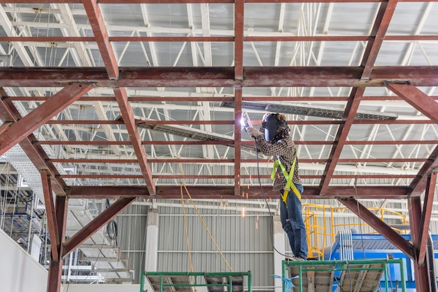 Technicians are welding steel structure. construction site image for the background.