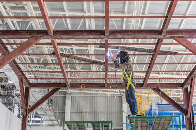 技術者は鋼構造を溶接している。背景の建設現場イメージ。