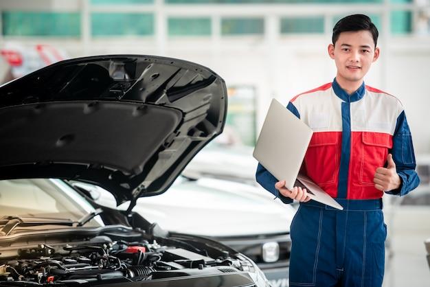 技術者がガレージで車をチェックして修理する自動車修理工場の技術者は、コンピューターシステムを使用してエンジンの問題(車の修理サービス、メンテナンスの概念)をチェックします。