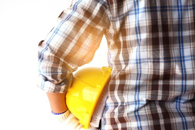 黄色いヘルメットを保持している建築の技術者