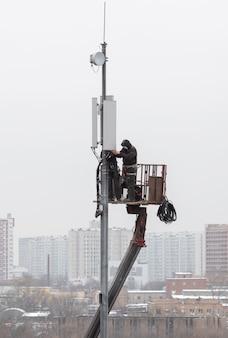 技術者は、モバイル信号増幅デバイスをタワーに設置します。