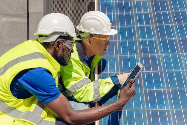 Техники обслуживают солнечную панель и проверяют ячейку, работающую с планшетом, для концепции альтернативной возобновляемой зеленой энергии дома