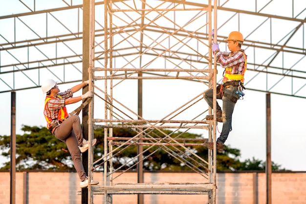 Technicians in safety clothing climbing scaffolding