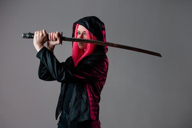 テクノサイバーパンクスタイル、未来の忍者、刀と黒い服を着たピンクの髪の若い女性、灰色のスタジオ写真