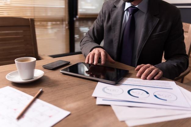 技術的成果。ハンサムな成功した実業家によって使用されている間、ドキュメントのテーブルの上に横たわっている現代の革新的な黒いタブレットのクローズアップ