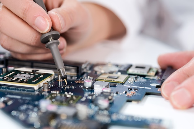 Technological background with closeup on tester checking motherboard.