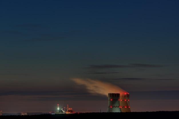 Технологический корпус атомной электростанции на фоне сумеречного неба. сигнальные огни для авиационной безопасности.