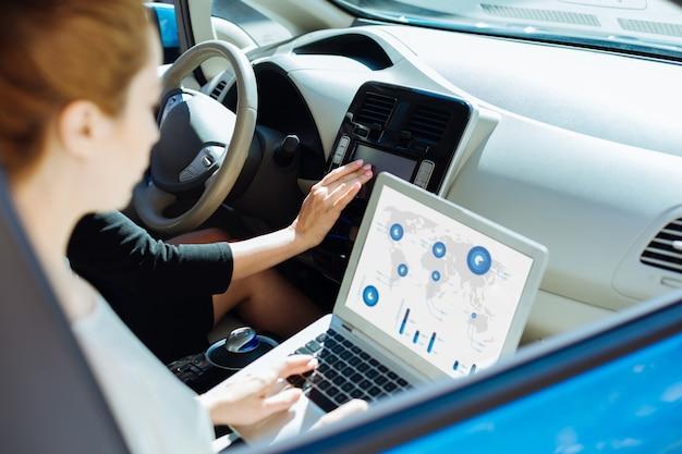 Технологическое устройство. крупный план современного инновационного ноутбука, используемого позитивными и трудолюбивыми хорошими деловыми женщинами в машине