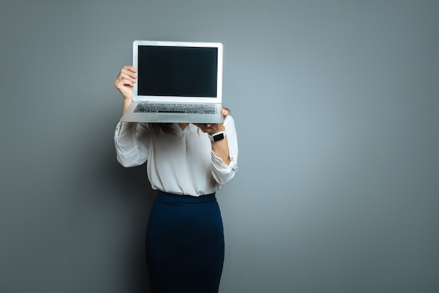Technological device. nice pleasant young woman holding her laptop and hiding her face behind it while standing against grey background