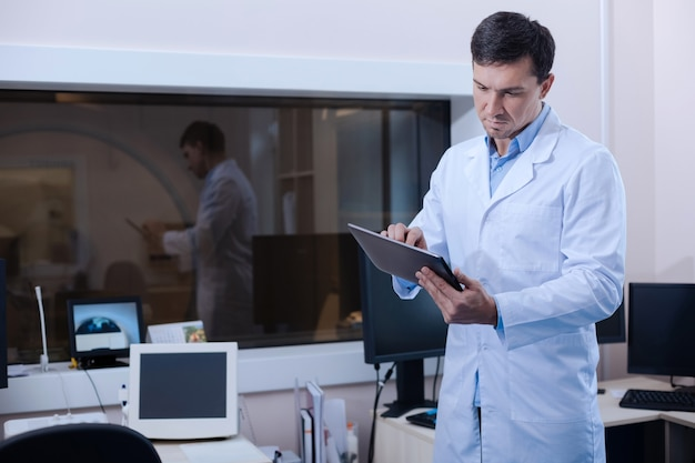 Technological device. professional experienced good looking doctor holding a tablet and using it while standing in the laboratory
