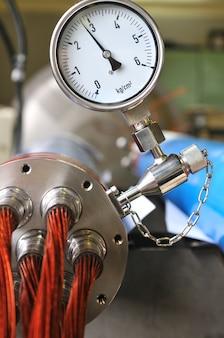 技術機器、切断された細いワイヤーの束が突き出ている金属デバイスの圧力測定。