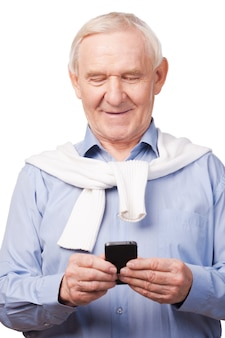 Technological wonders of nowadays. happy senior man holding mobile phone while standing against white background