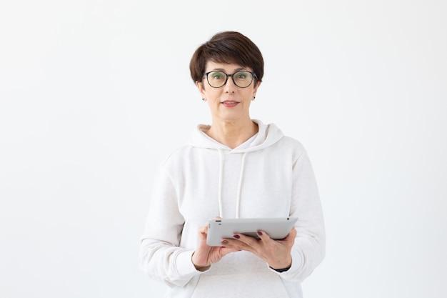 Концепция технологий и современных людей - красивая женщина 50 лет с короткими волосами, держащая таблетку на белом фоне.