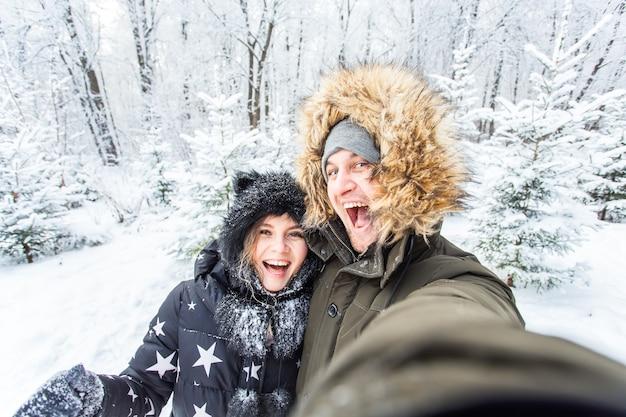 技術と関係の概念-外の冬の森で自分撮りをしている幸せな笑顔のカップル。