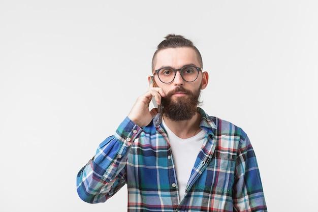 テクノロジー、コミュニケーション、人のコンセプト。ひげを生やしたクールな男が携帯電話で話している