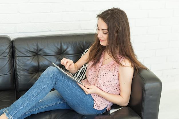 기술, 커뮤니케이션, 사람들이 개념-젊은 여자가 소파에 앉아 태블릿에서 채팅과 미소.