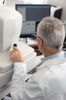 Технологии при обследовании. седовласый опытный офтальмолог с использованием технологий во время обследования