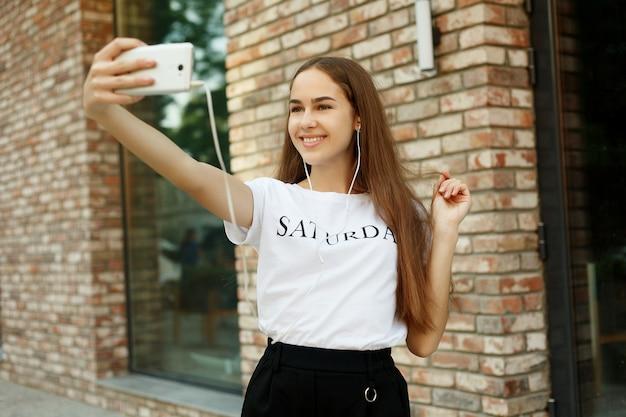 テクノロジー、感情、人々、美しさ、ファッション、ライフスタイルのコンセプト-のんきで幸せな、晴れた春の気分。魅力的な若い女性がカメラで自分撮りをしています。屋外の街を散歩している間