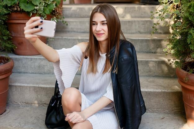 Технологии, эмоции, люди, красота, мода и концепция образа жизни - молодая красавица делает селфи для себя на смартфоне, портрет на открытом воздухе, фотомодель, красивая девушка, хипстер, красотка, уличная фотография