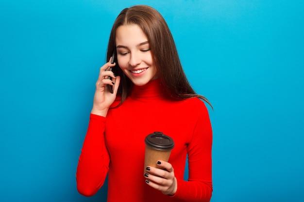 기술, 감정, 사람, 아름다움, 라이프 스타일 개념 - 빨간 블라우스에 감정적인 행복 한 아름 다운 여자 사랑 스러운 초상화 아름 다운 여자 전화 얘기 하 고 테이크 아웃 커피를 들고입니다. 파란색 배경
