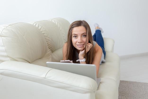 テクノロジー、フリーランス、人々のコンセプト-ノートパソコンでソファに横になってカメラを見ているかなり若い女性