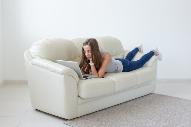 Technologies, freelance and people concept - pretty young woman lying on sofa with laptop